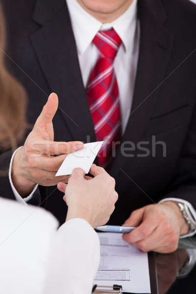 Businessman Giving Visiting Card To Colleague At Desk Stock photo © AndreyPopov