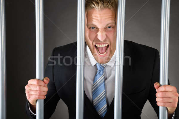 Aggressive Businessman Behind Bars Stock photo © AndreyPopov