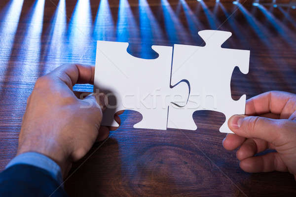 Close-up Of A Person Joining Two Jigsaw Pieces Stock photo © AndreyPopov