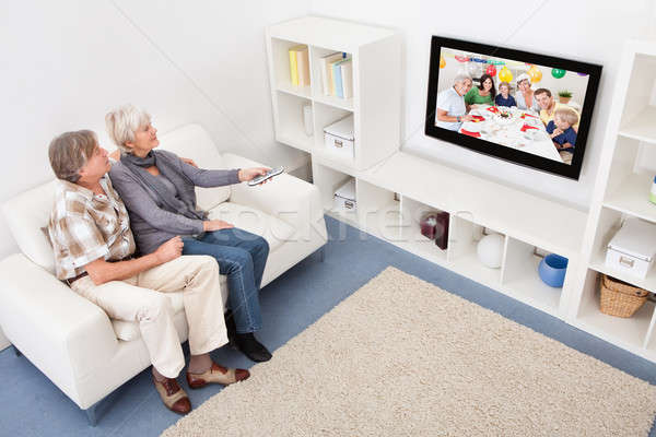 Senior Couple Changing Channel Of Television Stock photo © AndreyPopov