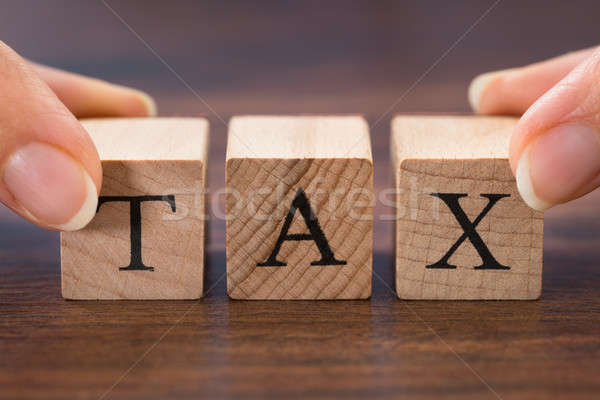 Person Hand Holding The Word Tax Stock photo © AndreyPopov