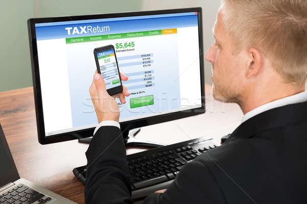 üzletember néz online adó visszatérés űrlap Stock fotó © AndreyPopov