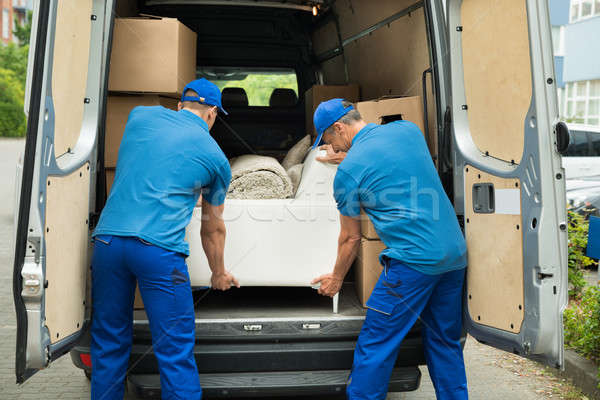 Two Workers Adjusting Sofa In Truck Stock photo © AndreyPopov