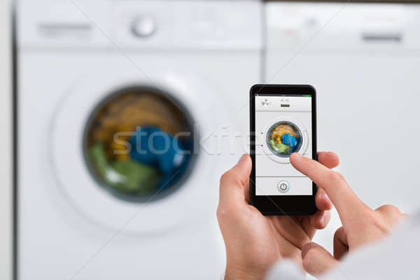 Stock photo: Person Hands With Mobile Phone Operating Washing Machine