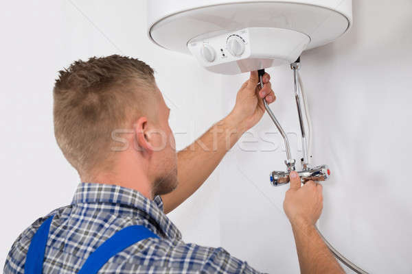 Worker Fixing Electric Boiler Stock photo © AndreyPopov