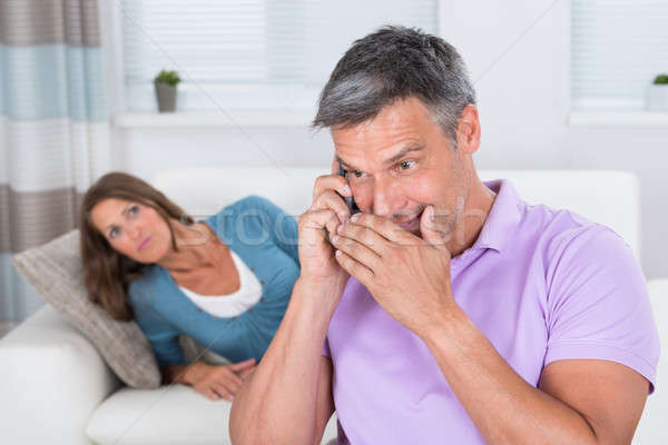 Woman Looking At Man Talking On Mobile Phone Stock photo © AndreyPopov
