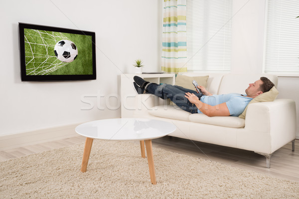 Homme regarder football match maison Photo stock © AndreyPopov