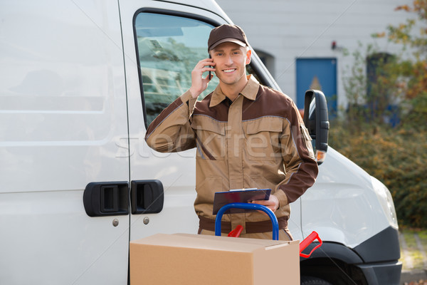 Delivery Man Using Mobile Phone Against Truck Stock photo © AndreyPopov