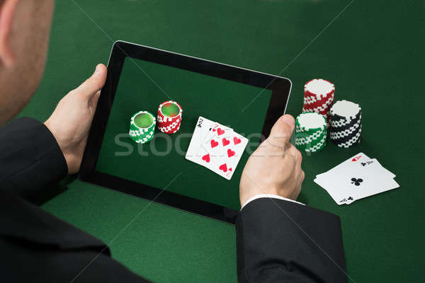 Poker Hand With Digital Tablet Showing Chips And Cards Stock photo © AndreyPopov