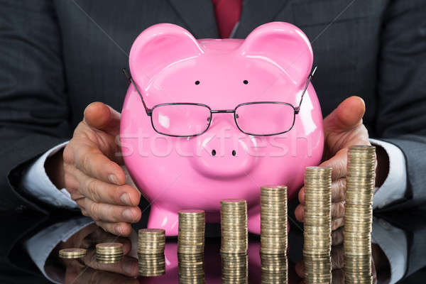 Close-up Of Businessman Hand Sheltering Piggybank And Coins Stock photo © AndreyPopov