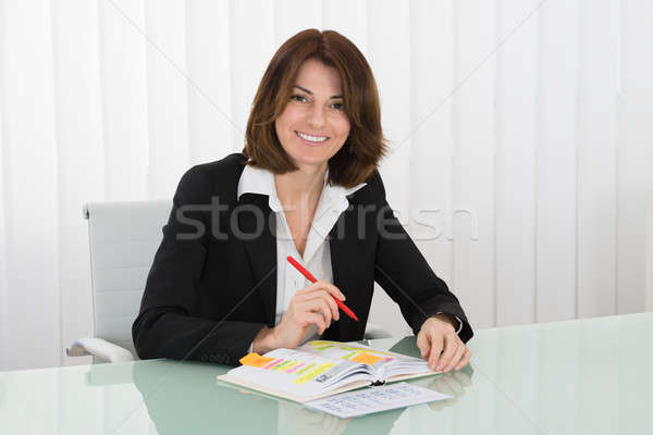 Businesswoman With Calendar Writing Schedule In Diary Stock photo © AndreyPopov