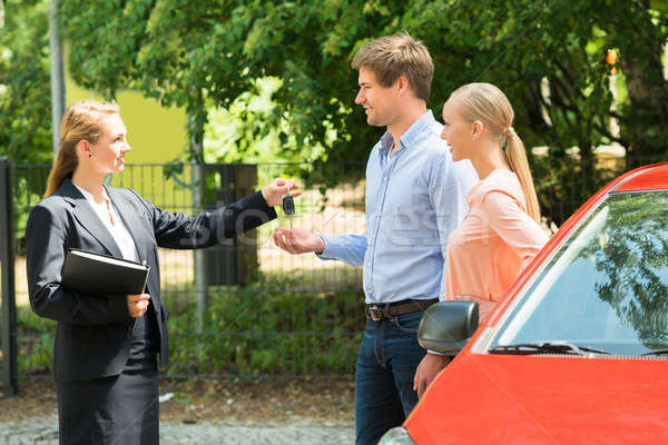 Saleswoman Giving Car Key To Couple Stock photo © AndreyPopov