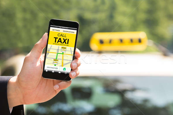 Person Hand Holding Mobile Phone Booking Taxi Stock photo © AndreyPopov
