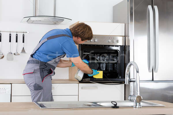 Stock photo: Man In Overall Cleaning Oven