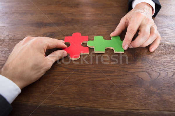 Stock photo: Two Businessmen Joining Jigsaw Pieces