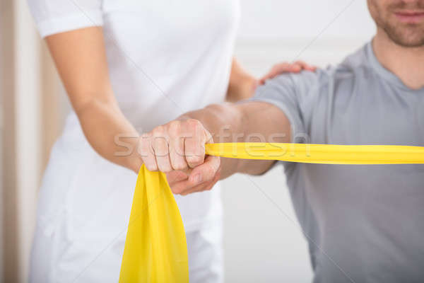 Physiotherapist Giving Man A Training With Exercise Band Stock photo © AndreyPopov