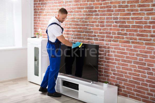 Mężczyzna woźny czyszczenia telewizji uniform szmata Zdjęcia stock © AndreyPopov