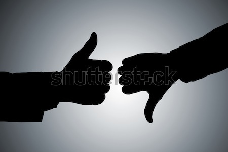 Silhouette Of Hands Showing Thumb Up And Thumb Down Stock photo © AndreyPopov