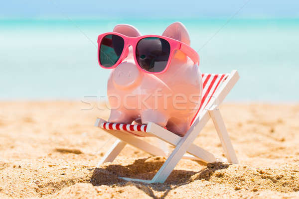Pink Piggy Bank On The Deck Chair At Beach Stock photo © AndreyPopov