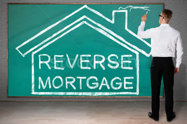 Businessman Drawing House With Reverse Mortgage Text Stock photo © AndreyPopov