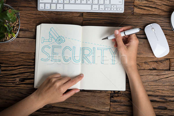 Stock photo: Human Hand With Security Text On Notebook