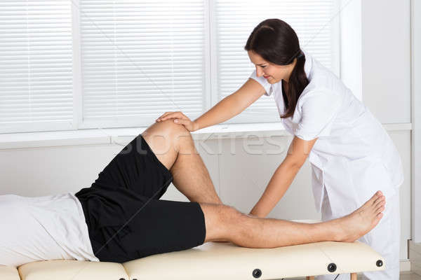 Physiotherapist Giving Leg Exercise In Clinic Stock photo © AndreyPopov