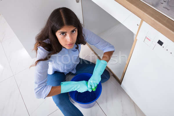 Woman Squeezing Water In Bucket Stock photo © AndreyPopov