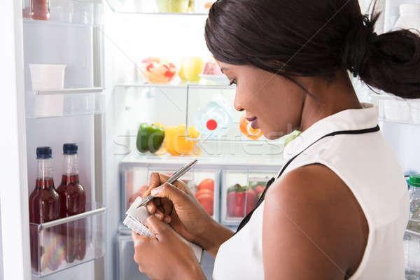 Woman Writing On Spiral Book Near Refrigerator Stock photo © AndreyPopov