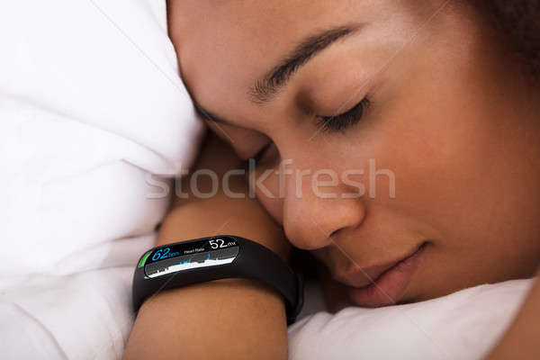 Woman Sleeping On Bed With Smartwatch Stock photo © AndreyPopov