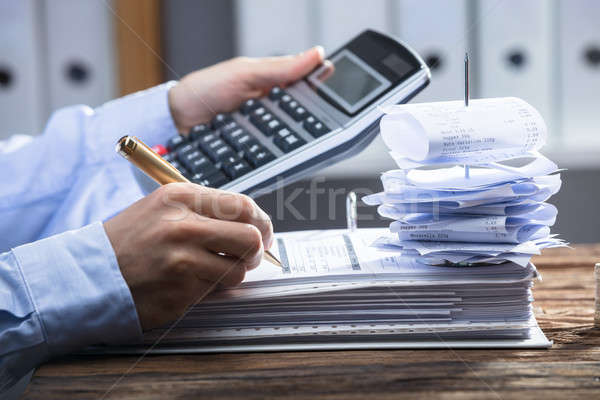 Businessperson Using Calculator For Calculating Invoice Stock photo © AndreyPopov
