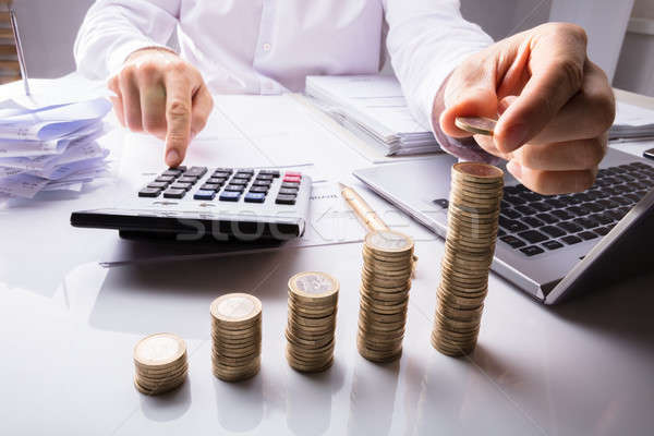 Business Person Counting Coins Using Calculator Stock photo © AndreyPopov