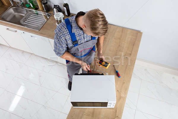 Male Technician Checking Microwave Stock photo © AndreyPopov