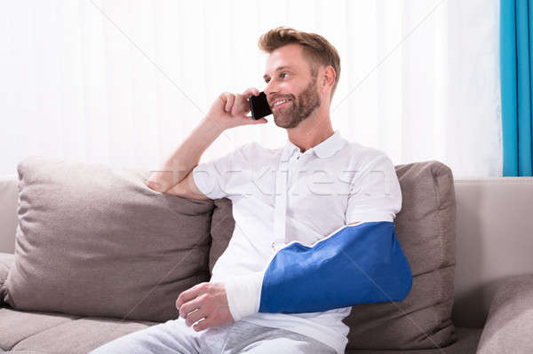 Man With Fractured Hand Talking On Mobile Phone Stock photo © AndreyPopov