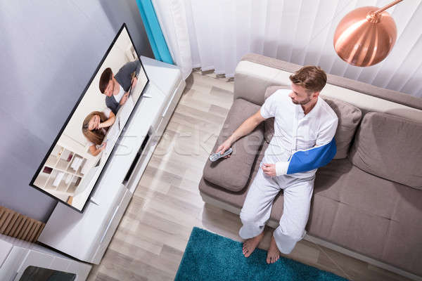 Man With Fractured Hand Watching Television Stock photo © AndreyPopov