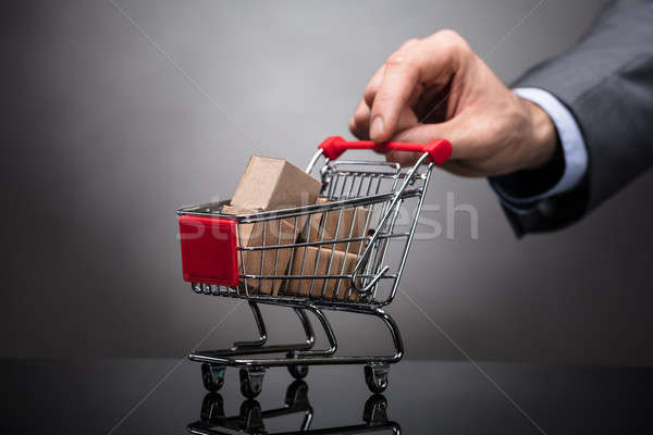 Businessperson Holding Shopping Cart With Cardboard Boxes Stock photo © AndreyPopov