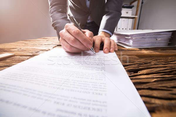 Empresario firma documento primer plano escritorio Foto stock © AndreyPopov