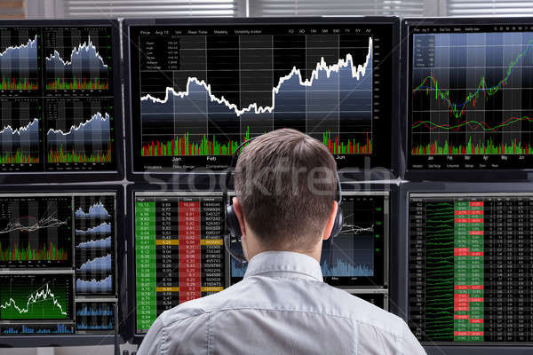 Stock Market Broker Analyzing Graphs On Computer Screens Stock photo © AndreyPopov