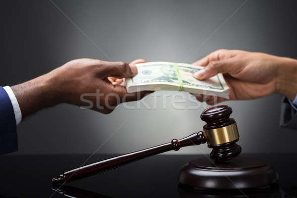 Gavel And Mallet In Front Of Hands Exchanging Banknotes Stock photo © AndreyPopov
