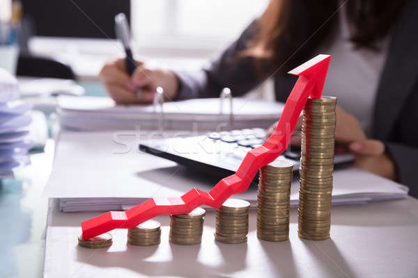 Increasing Golden Coins With Red Arrow Showing Upward Direction Stock photo © AndreyPopov