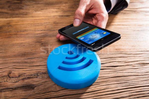 Ludzka ręka smartphone niebieski bezprzewodowej ikona Zdjęcia stock © AndreyPopov