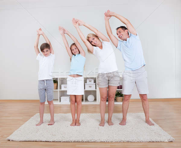 Family Doing Stretching Exercises On The Carpet Stock photo © AndreyPopov