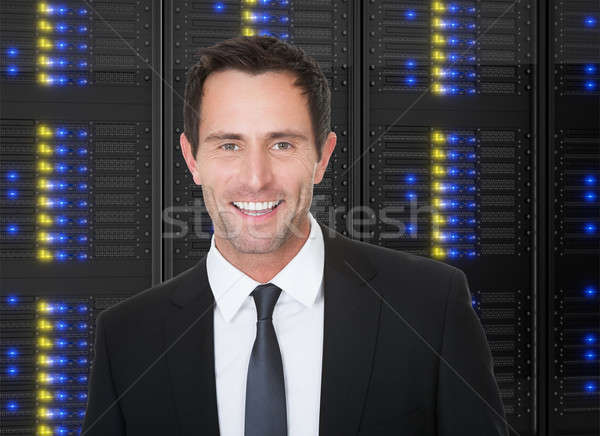 Businessman standing in front of server racks Stock photo © AndreyPopov