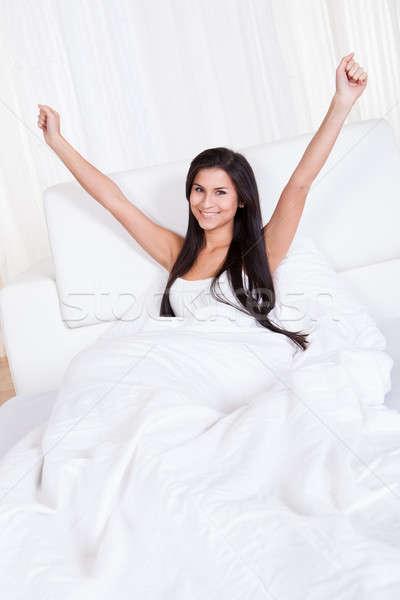 Fiatal nő ujjongás ágy karok fölött fej Stock fotó © AndreyPopov