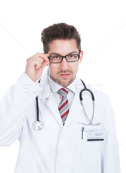 Confident Young Male Doctor Adjusting Glasses Stock photo © AndreyPopov