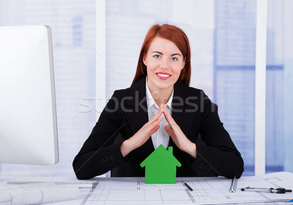 Businesswoman Sheltering Green House Model Stock photo © AndreyPopov
