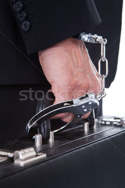 Hand With Handcuff Holding Suitcase Stock photo © AndreyPopov