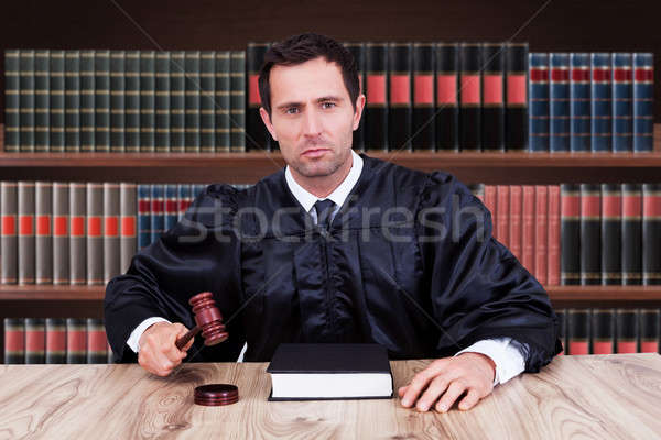 Confident Judge Striking Gavel In Courtroom Stock photo © AndreyPopov