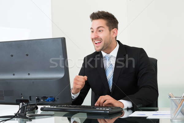 Successful Businessman Looking At Monitor At Desk Stock photo © AndreyPopov