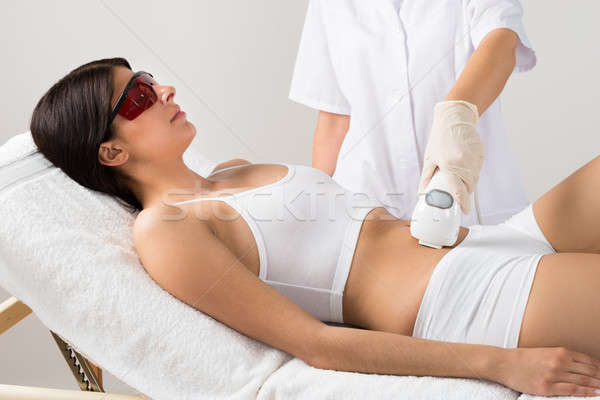 Young Woman Receiving Laser Treatment On Belly Stock photo © AndreyPopov