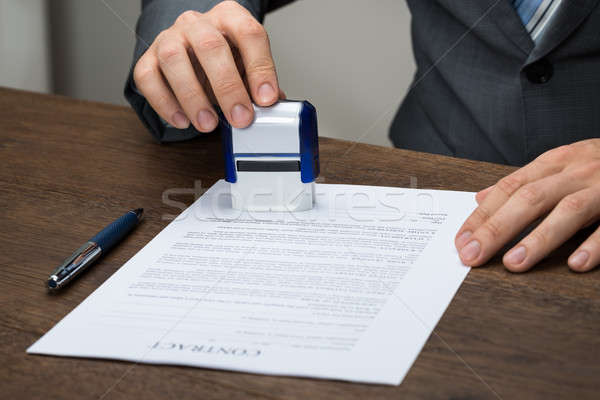 Businessman Stamping Document Stock photo © AndreyPopov
